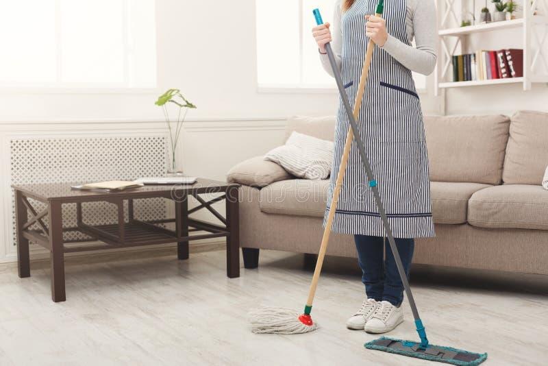 Casa irreconocible de la limpieza de la mujer con las fregonas foto de archivo