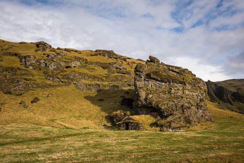 Casa islandêsa do relvado construída em uma caverna da rocha imagem de stock