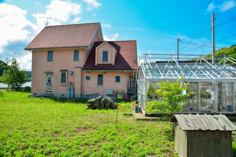 Casa japonesa na vila com estufa fotografia de stock royalty free