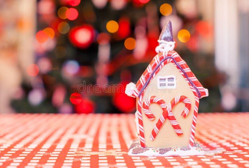 Casa leggiadramente del pan di zenzero decorata dalle caramelle variopinte su un fondo dell'albero di Natale luminoso con la ghir immagini stock
