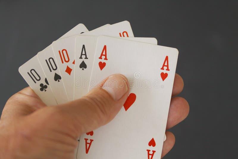 Casa llena de la mano de póker con tres tarjetas de diez y dos as - cercanos para arriba en fondo negro foto de archivo