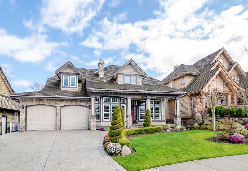 Casa luxuosa com ajardinar bonito em um dia ensolarado imagem de stock
