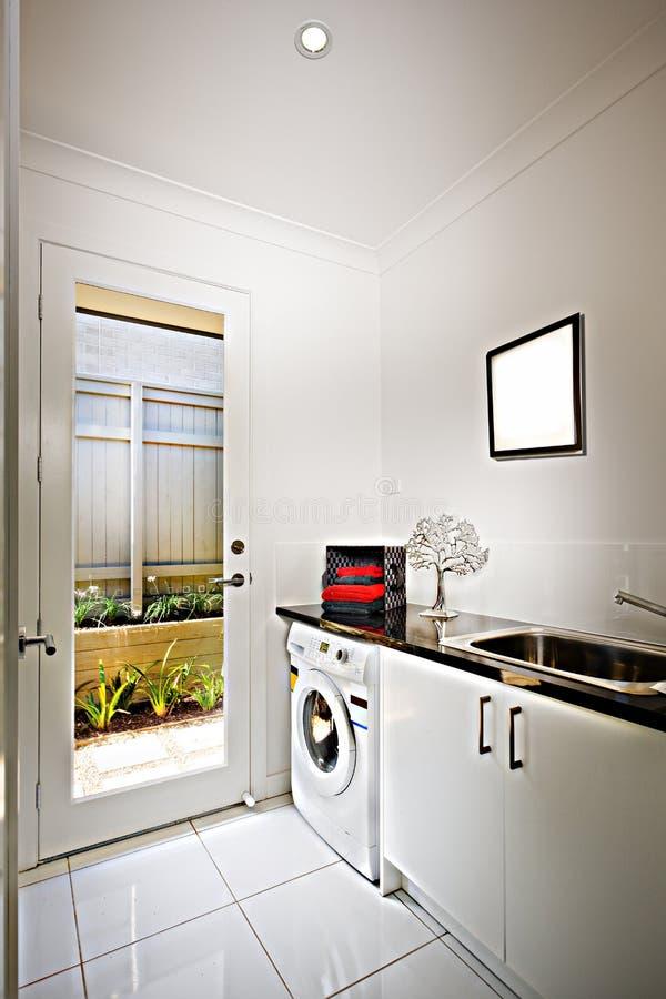 Casa luxuosa com uma cozinha e uma máquina de lavar que incluem um contador de prata na entrada do armário e da porta fotos de stock royalty free