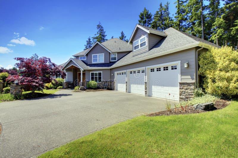 A casa luxuosa exterior com janelas francesas e três espaçam a garagem de estacionamento imagens de stock
