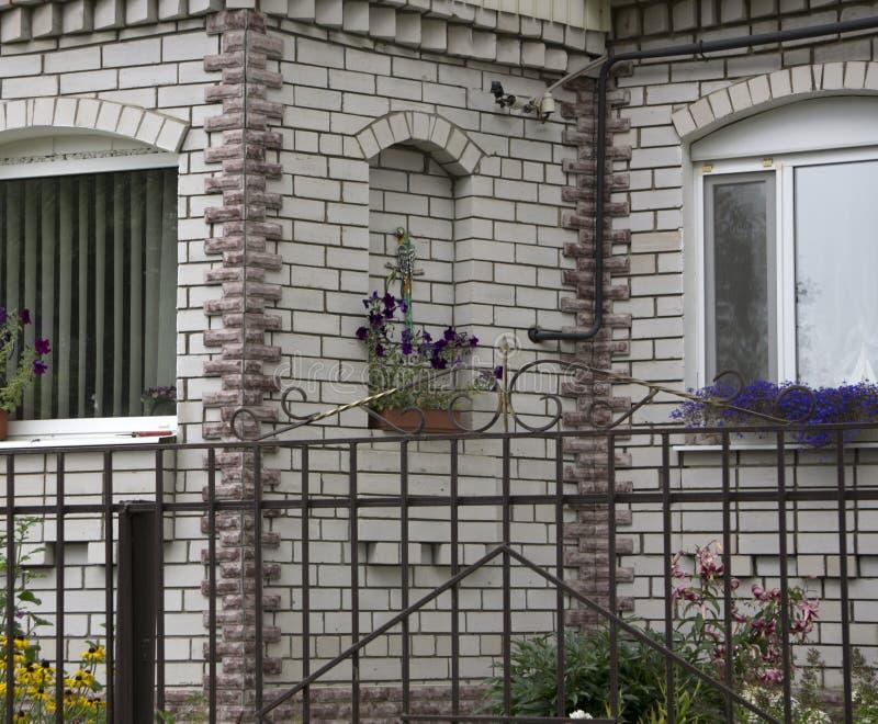 Casa luxuosa feito-à-medida grande com jardim da frente agradavelmente ajardinado e entrada de automóveis à garagem nos subúrbios imagem de stock royalty free