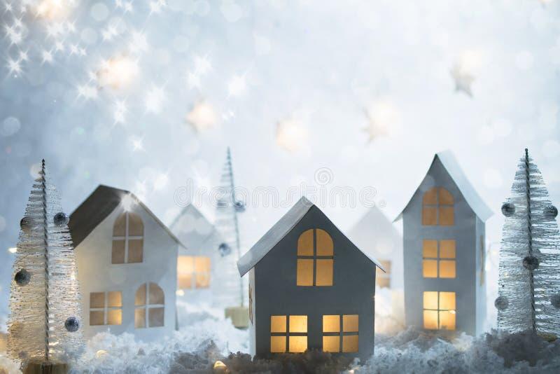 Casa magica miniatura del nuovo anno e di Natale nella neve alle luci della città del bokeh e di notte Decorazioni di natale immagine stock