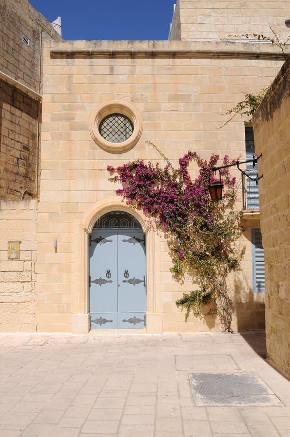 Casa maltesa com flores e a porta azul ornamentado fotografia de stock