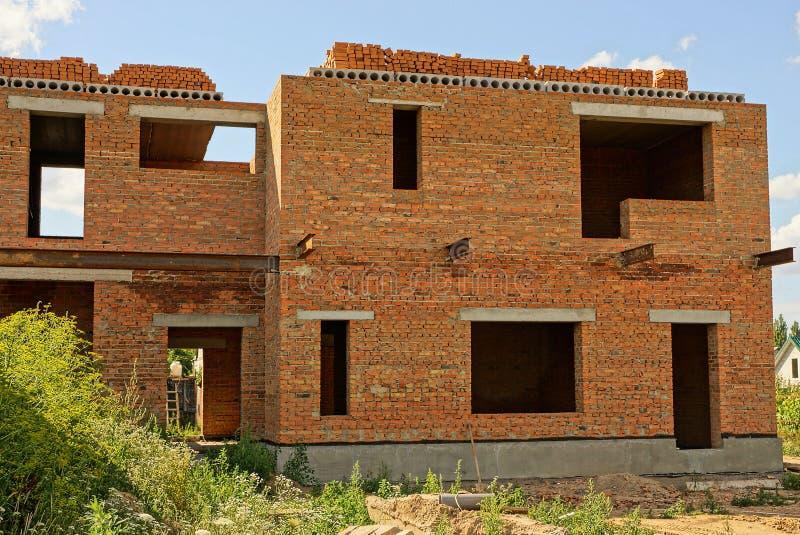 Casa marrón inacabada grande del ladrillo en hierba verde fotos de archivo