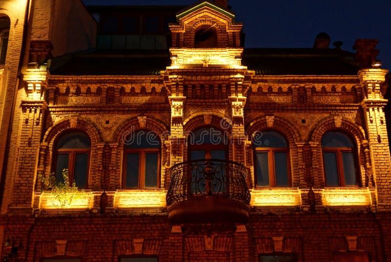 casa marrom velha do tijolo com janelas e um balcão com iluminação na rua da noite fotos de stock royalty free