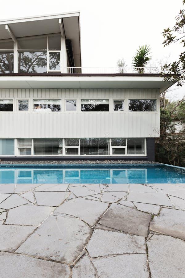 Casa meados de do século exterior com piscina e craz telhados azuis fotografia de stock royalty free