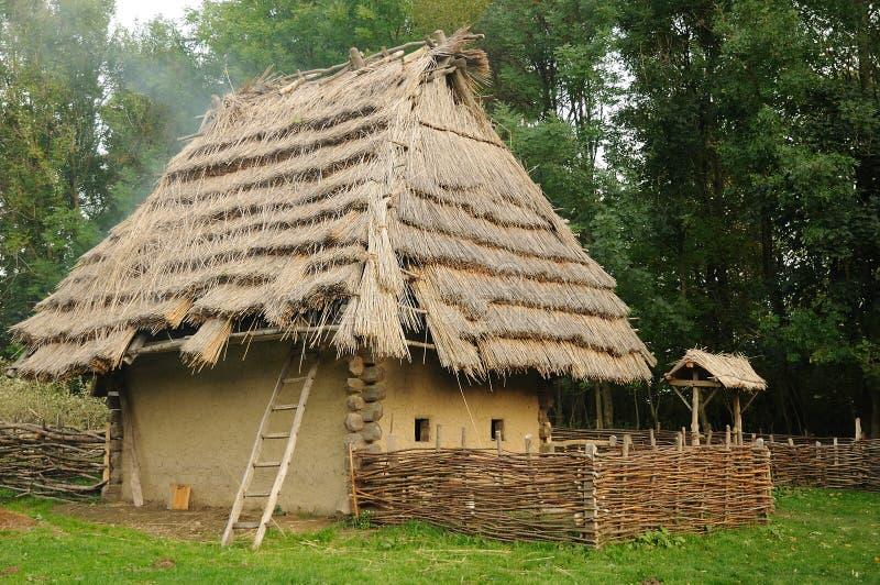 Casa medieval con el tejado de la paja imagenes de archivo