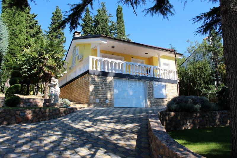 Casa Mediterranea moderna con la strada privata di pietra ed i grandi alberi fotografie stock libere da diritti