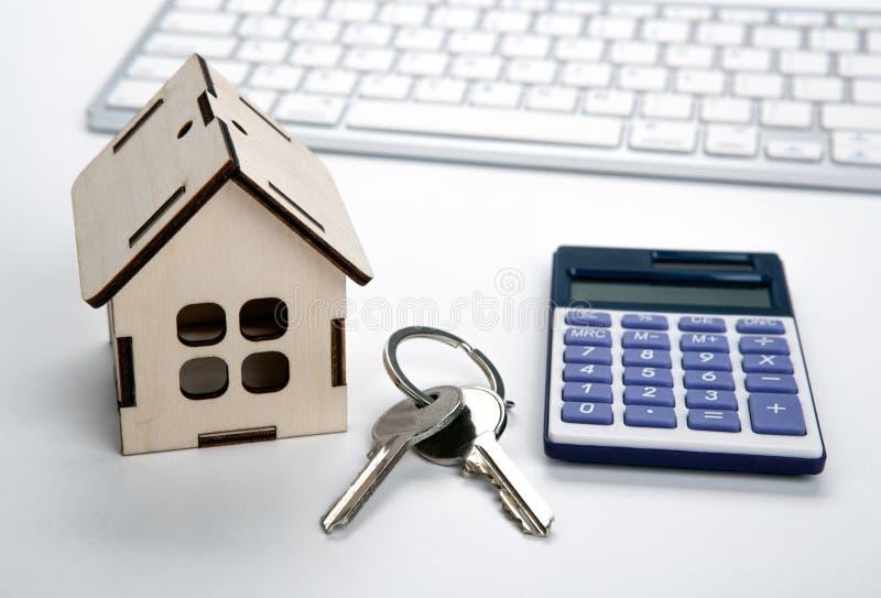 Casa miniatura de madera con llaves de la puerta y una calculadora fotos de archivo libres de regalías