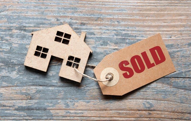 Casa miniatura del bene immobile con l'etichetta venduta immagini stock