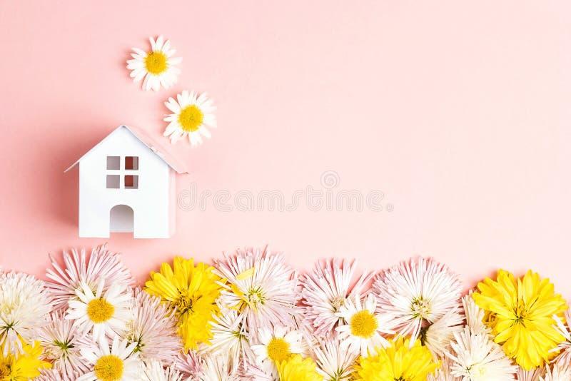 Casa miniatura del juguete con las flores y spase de la copia en backgrou rosado imagenes de archivo