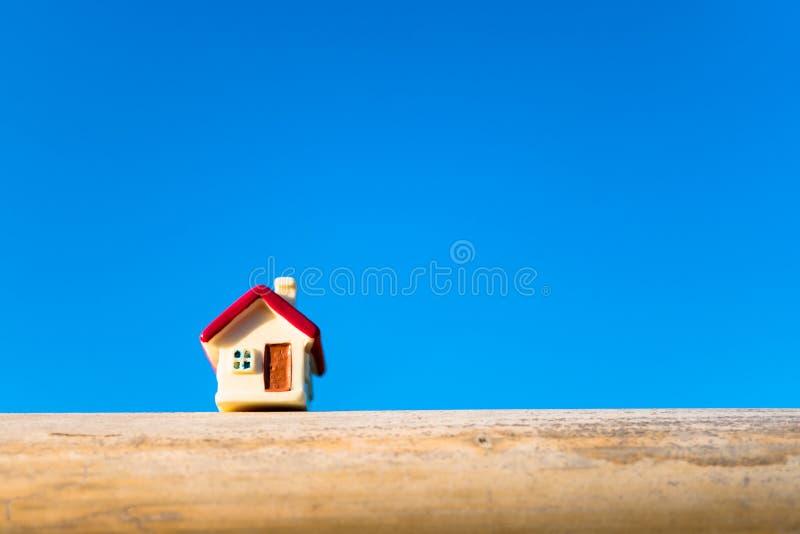 Casa miniatura del primo piano sul fondo del cielo blu usando come proprietà fotografie stock
