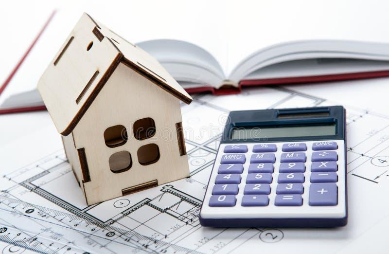 Casa miniatura di legno con un calcolatore e un disegno fotografie stock