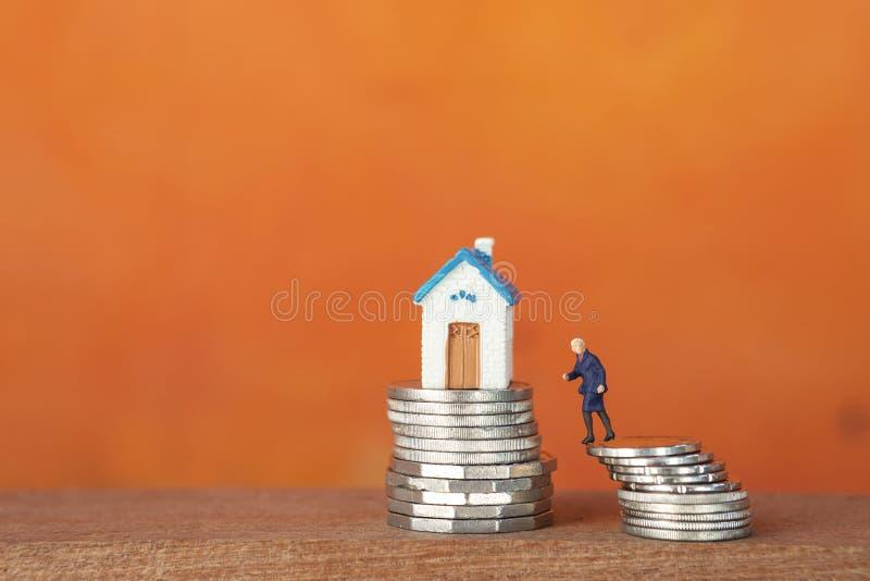Casa miniatura e ragazza miniatura di affari sulla pila della moneta d'argento sopra fondo arancio vago immagini stock