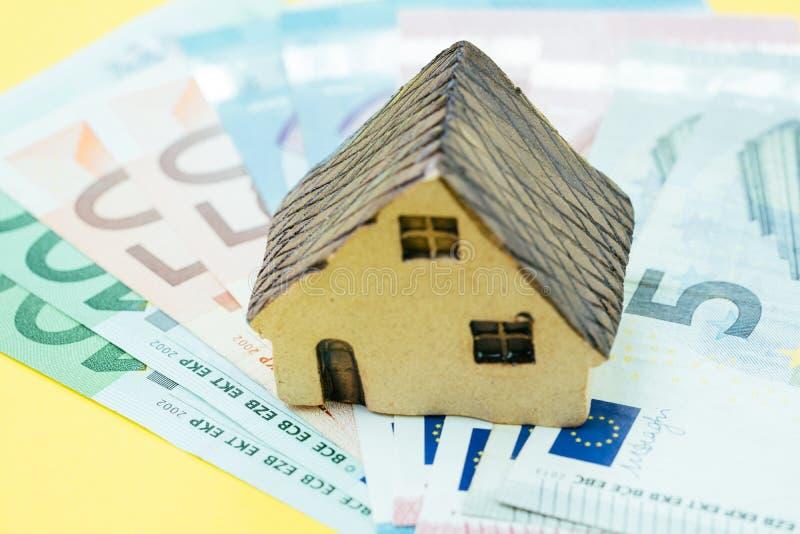 Casa miniatura en pila de dinero euro del billete de banco usando como hipoteca, inversión inmobiliaria, préstamo hipotecario o c imágenes de archivo libres de regalías