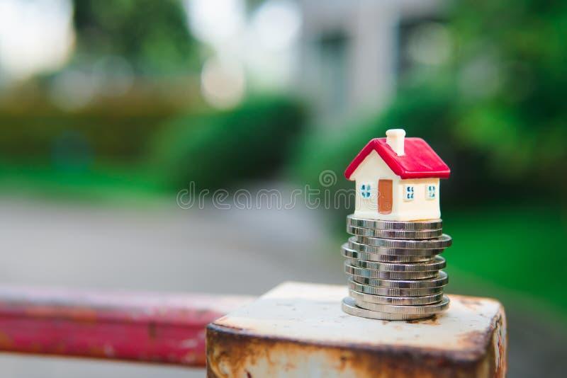 Casa miniatura sulle monete della pila usando come concetto della proprietà immagine stock libera da diritti
