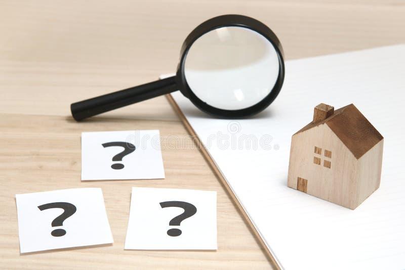 Casa miniatura y muchos signos de interrogación en los Libros Blanco Casa con los signos de interrogación y la lupa Concepto 6 de imagen de archivo libre de regalías