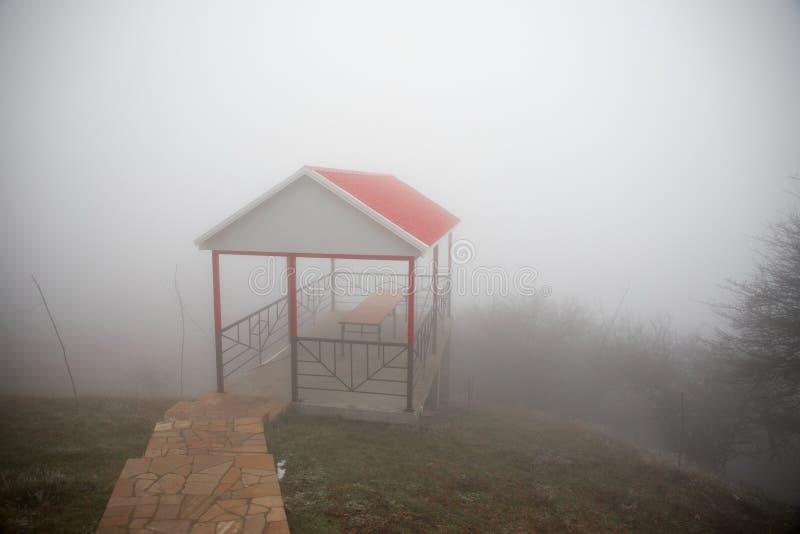 Casa misteriosa nella foresta con nebbia e un albero La vecchia casa spettrale sulla terra di in nessun posto fotografia stock