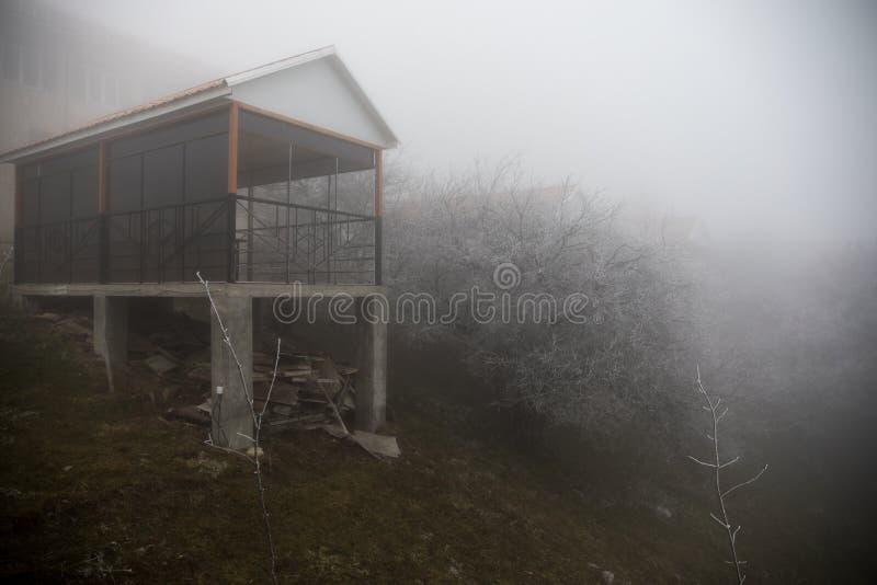Casa misteriosa nella foresta con nebbia e un albero La vecchia casa spettrale sulla terra di in nessun posto immagine stock libera da diritti