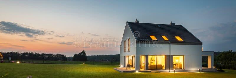 Casa moderna con il giardino alla notte fotografie stock libere da diritti
