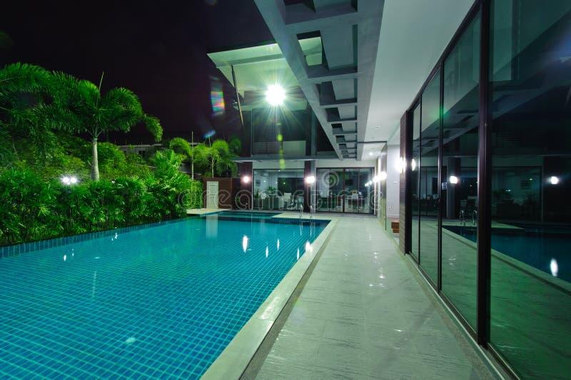 Casa moderna con la piscina alla notte immagini stock libere da diritti