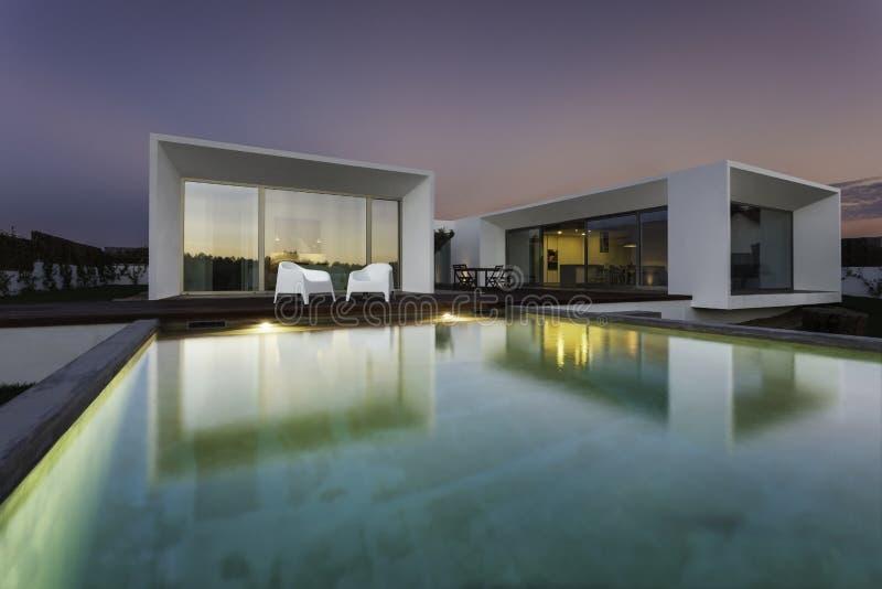 Casa moderna con la piscina del giardino e la piattaforma di legno immagini stock