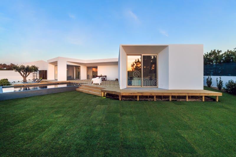 Casa moderna con la piscina del giardino e la piattaforma di legno fotografie stock libere da diritti