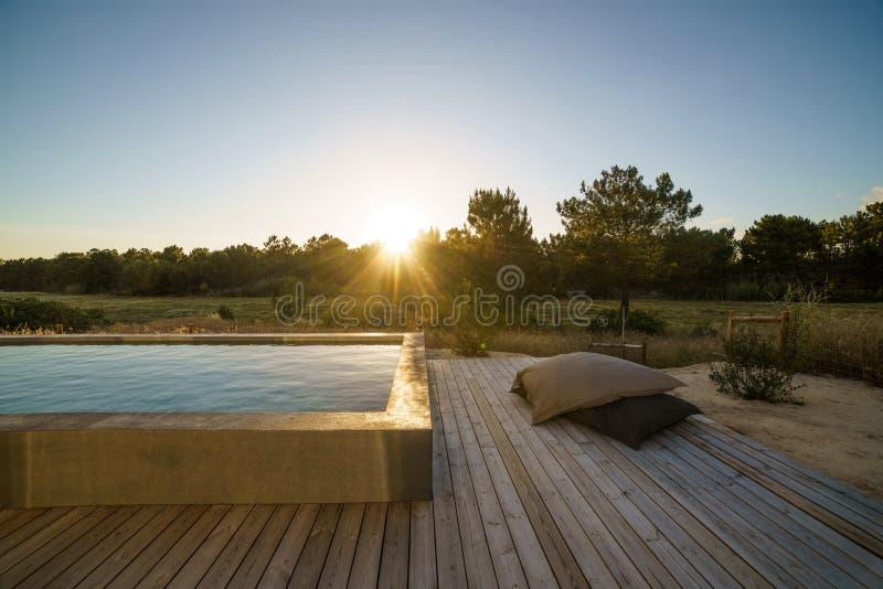 Casa moderna con la piscina del giardino e la piattaforma di legno fotografia stock
