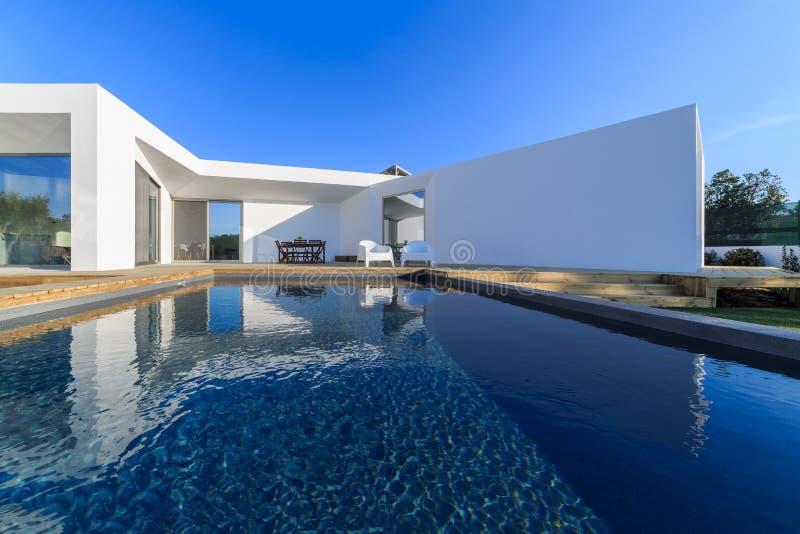 Casa moderna con la piscina del jard n y la cubierta de for Casa de madera con jardin