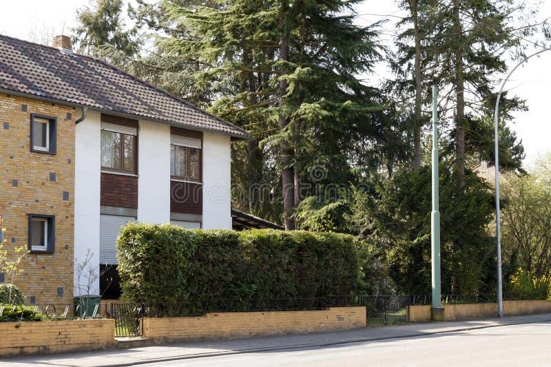 Casa moderna da família na rua rural cercada com árvores verdes foto de stock
