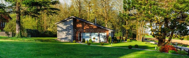 Casa moderna della famiglia nel posto calmo della natura, tempo di tramonto fotografia stock libera da diritti