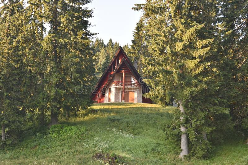 A casa moderna do estilo bonito da montanha na floresta fotos de stock royalty free