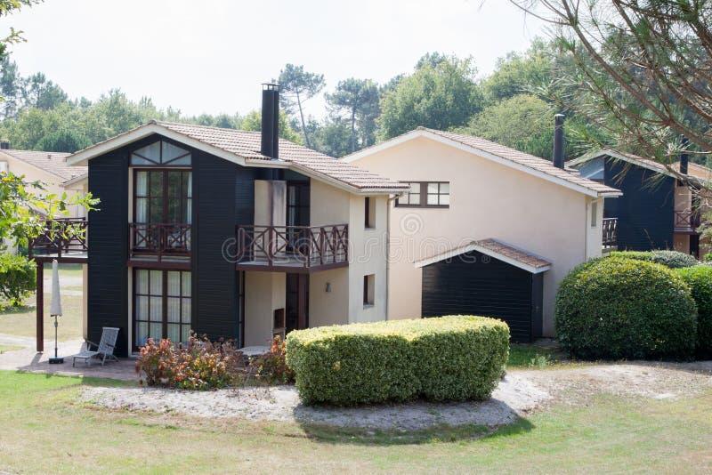 Casa moderna en el cemento y la madera, visión desde el jardín fotografía de archivo