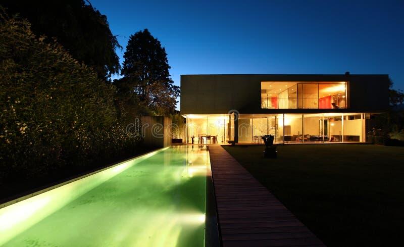 Casa moderna hermosa al aire libre en la noche imagenes de archivo