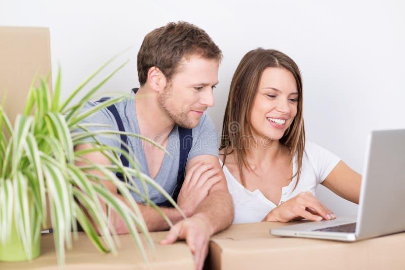 Casa movente dos pares novos que olha um portátil foto de stock