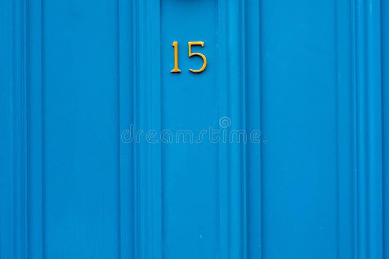 Casa número 15 con los quince en los dígitos de bronce del metal en una puerta azul imágenes de archivo libres de regalías