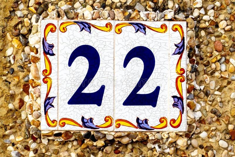 Casa número 22 en azul en el azulejo blanco de la teja con la frontera pintada fotos de archivo