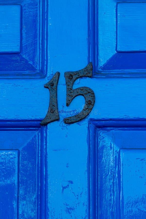Casa número 15 en una puerta principal de madera azul foto de archivo libre de regalías