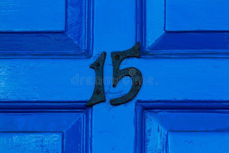Casa número 15 en una puerta principal de madera azul fotos de archivo