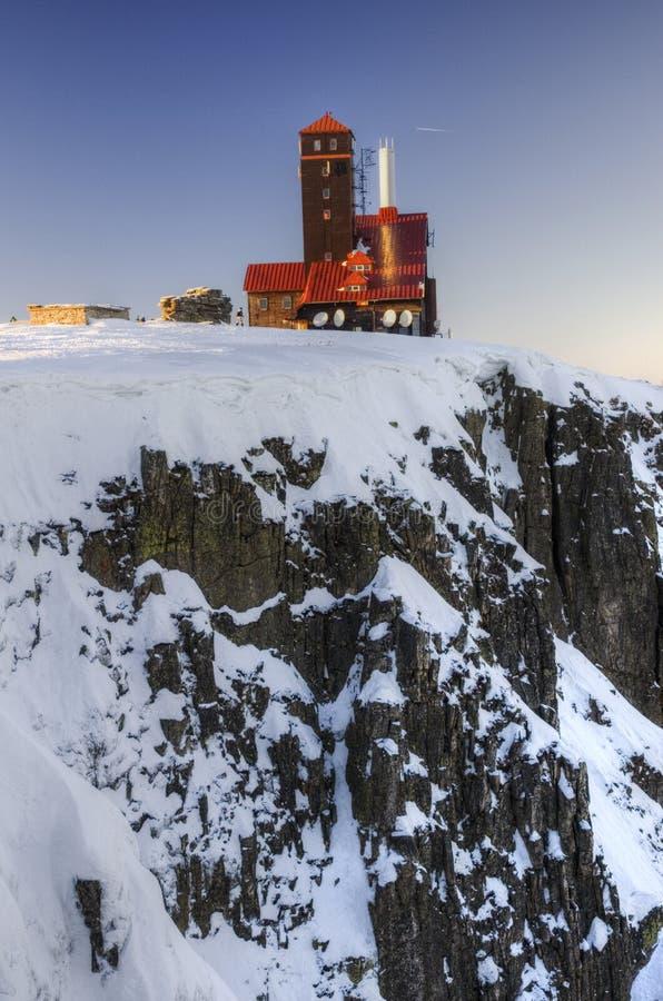 Casa na rocha da montanha do inverno imagem de stock royalty free