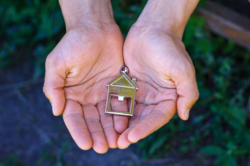 Casa nas mãos do conceito de comprar bens imobiliários fundo natural imagens de stock royalty free