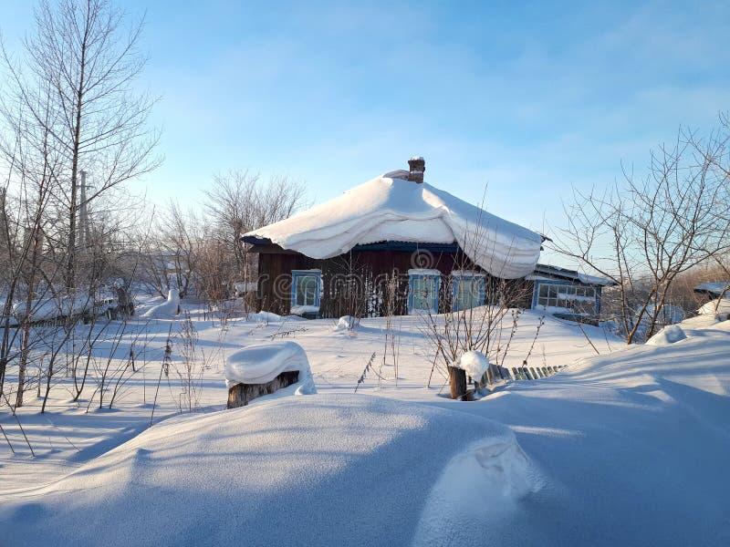 Casa nevado da vila em Sibéria foto de stock royalty free