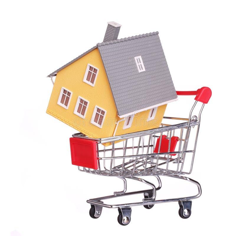 Casa no carrinho de compras isolado Conceito da hipoteca fotografia de stock royalty free