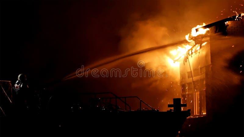 Casa no fogo conflagration O bombeiro luta o fogo foto de stock