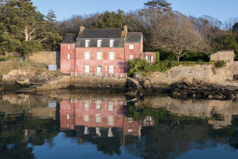 Casa no Ile-auxiliar-Moines Golfo de Morbihan com reflexões em t fotografia de stock