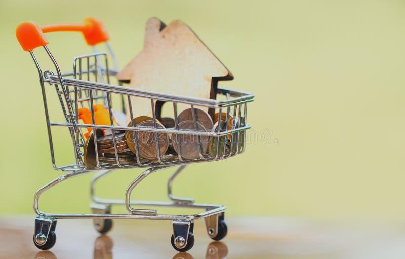 Casa no mini carrinho de compras com a pilha de dinheiro das moedas para o investimento residencial imagens de stock